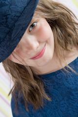 8 летняя девочка выглядывает из-под шляпы (студийный портрет)