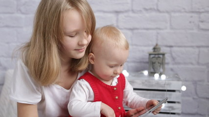 Girls playing on the tablet at home