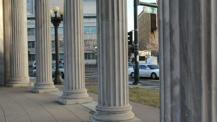 Pan shot through Roman columns to the city traffic