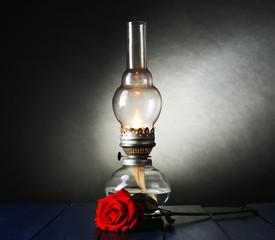 Kerosene lamp with red rose on wooden table on dark background