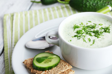 Cucumber soup in bowl on color wooden table background