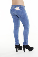 slim woman legs in jeans with euros in her pocket