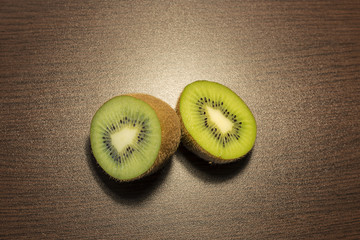 one kiwi in two halves on a table