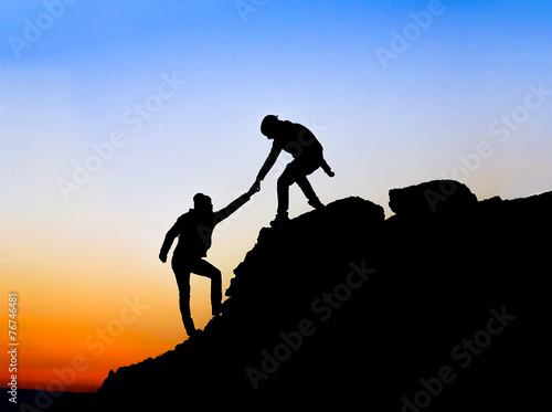 Silhouette of helping hand between two climber - 76746481