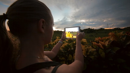 Woman using tablet PC to take photos of nature scenes