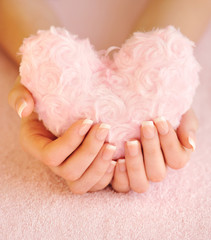 Fur pink heart in female hands