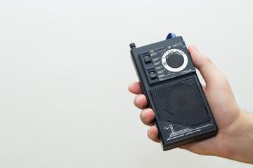 Portable retro radio receiver in hand.