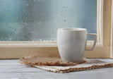 Fototapety Cup of hot drink with napkin on windowsill on rain background