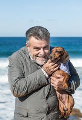 Attractive bearded man on the beach With red dachshund dog