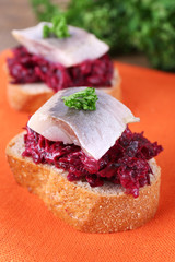 Rye toasts with herring and beets on napkin close up