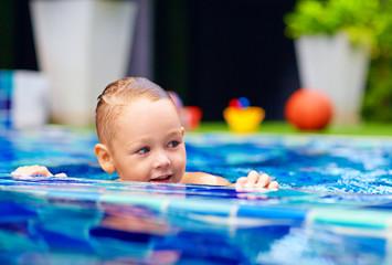 cute little boy swimming on pool
