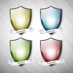 Empty isolated colored shields on dirty gray background. Vector