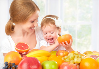 happy family mother and daughter eat healthy food,  fruit