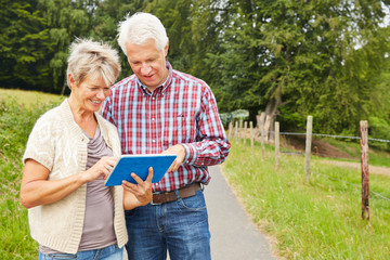 Paar Senioren navigiert mit Tablet Computer