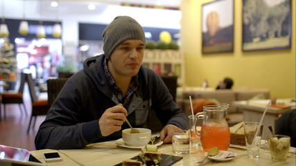 Man having tasty dinner in cafe and using pad