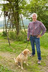 Jäger mit Hund vor Hochsitz