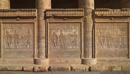 Hieroglyphic carvings on the exterior walls of an ancient egypti