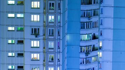 Timelapse of multistorey building with twilnkling lights in late