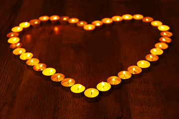 Burning candles in shape of heart on dark background