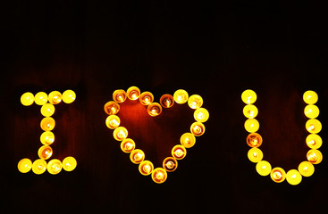Words I LOVE YOU formed by burning candles on dark background