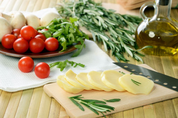 sliced cheese, tomatoes and herbs on a kitchen table