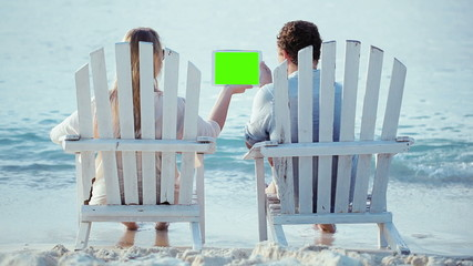 Woman and man sitting on the beach and looking at pad with green