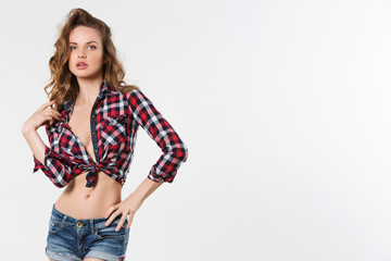 Portrait of sexy girl in checkered shirt and denim shorts.