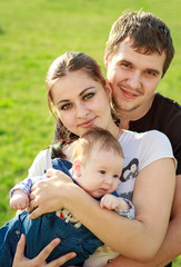 happy young family with baby in the park