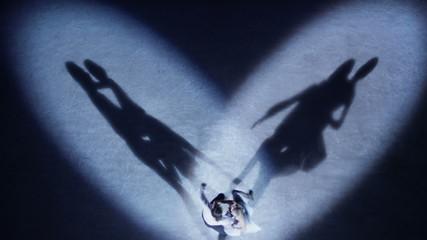 Figure skaters performing love dance in spotlight