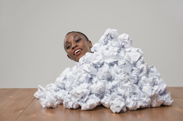 African business woman with crumpled pile of papers