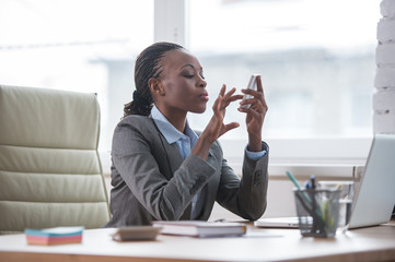 African Business woman texting with smartphone at office
