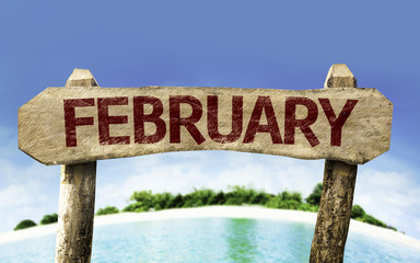February wooden sign with a beach on background