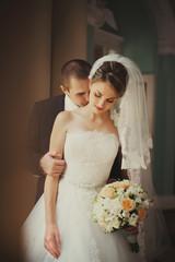 Closeup portrait handsome groom kissing bride in neck
