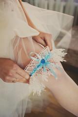 Bride putting a wedding garter on her leg