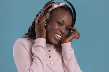 Happy African Woman listening to music on headphones
