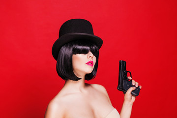 fashion beautiful model with pistol in hat cylinder, on red