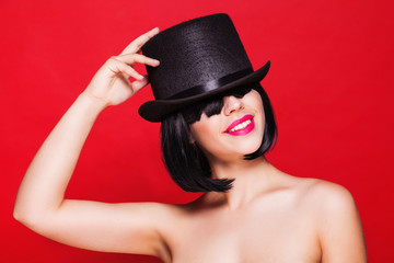 fashion beautiful model in hat cylinder, on red background