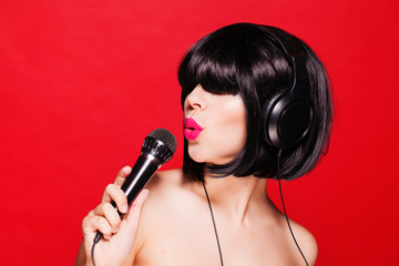 Woman listening to music on headphones and singing. Closeup