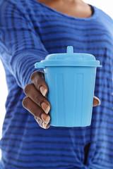 femme africaine tenant poubelle