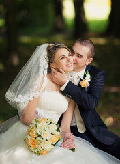 Elegant bride and groom posing together outdoors on a wedding da