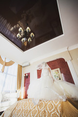 Happy bride jumping on the bed in the rich interior