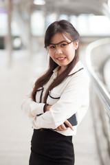Happy businesswoman standing on sidewalk.