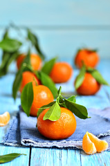 Tangerines with green leaves on a jeans napkin.