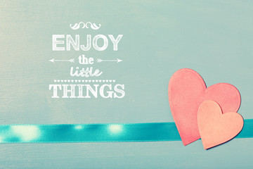 Enjoy the Little Things text with pink paper hearts