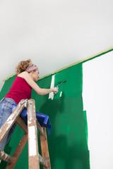 Frau malt Wand gruen