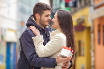 Romantic couple. Young man holding gift for his girlfriend
