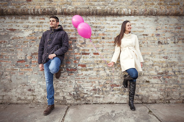 Young couple leaning on the wall holding pink balloons.