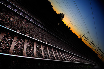 Railway tracks in sunset, city silhouette