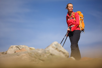 Pretty, young female hiker going uphill