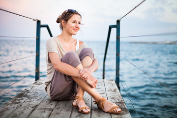 Portrait of a young woman on a jetty at the seacoast while on va
